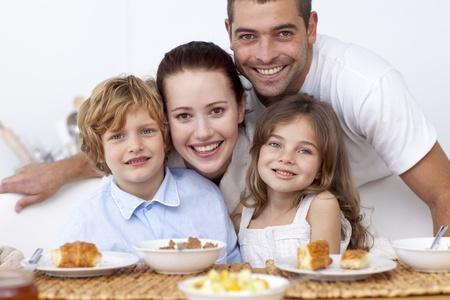 Children having breakfast with their parents photo