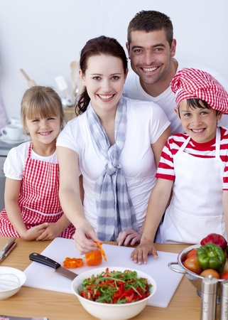 Family cutting colourful peppers in kitchen photo