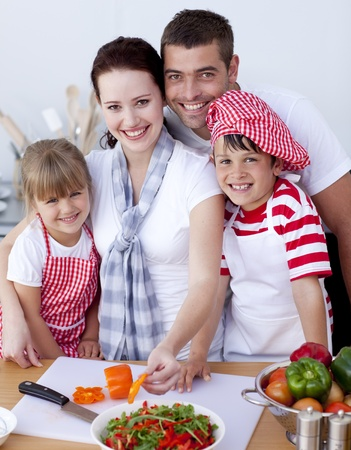 Family cutting colourful vegetables in kitchen photo