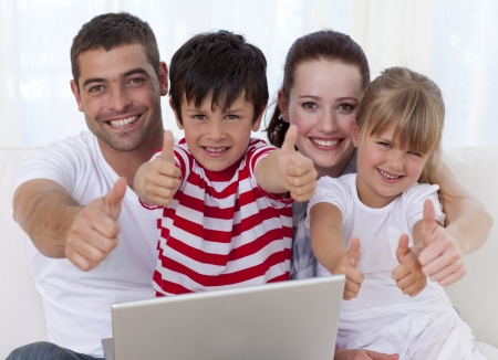 Family at home using a laptop with thumbs up photo