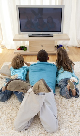 Family on floor in living-room watching television photo