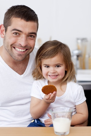 Father and daughter eating biscuits with milk photo