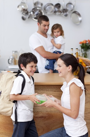 Smiling mother giving school lunch to her son photo