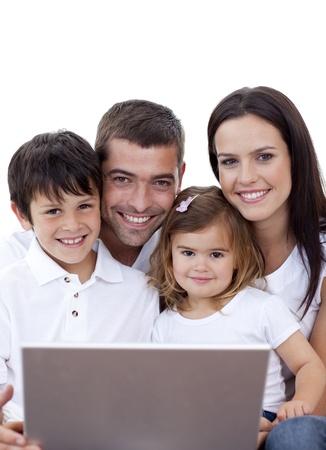 Retrato de joven familia usando un ordenador portátil en casa