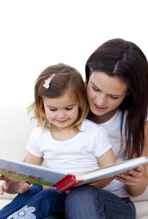 Mother and daughter reading a book on sofa photo