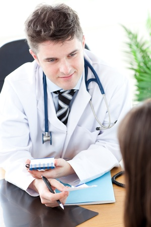 doctor giving pills: Confident male doctor giving pills to a paient Stock Photo