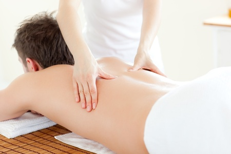 relaxation massage: Caucsasian young  man receiving a back massage Stock Photo