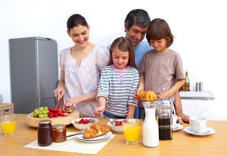 familia comiendo: Alegre familia desayunando un