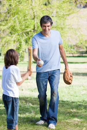 Adorable little boy playing baseball with his father photo