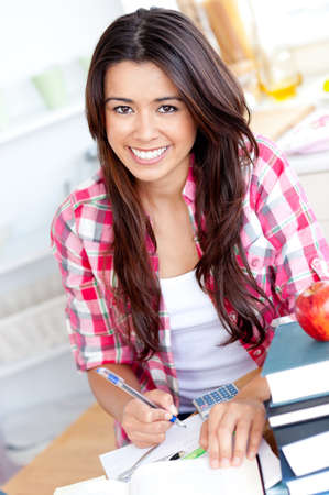 Portrait of a smiling  caucasian teen girl studying  at home photo