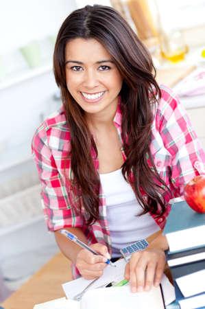 Portret van een glimlachende Kaukasische tiener meisje thuis studeren