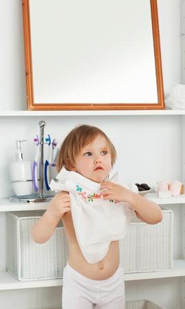 changing clothes: Peque�a ni�a cambia de ropa Foto de archivo