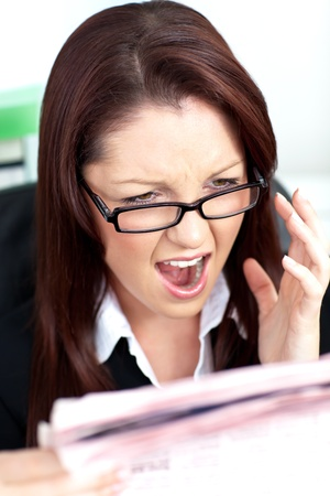 Angry businesswoman reading a newspaper photo