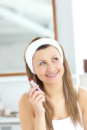 Positive woman holding a lipstick wearing a headband Stock Photo - 10131412