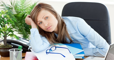 Bored businesswoman sitting at her desk  Stock Photo - 10134161