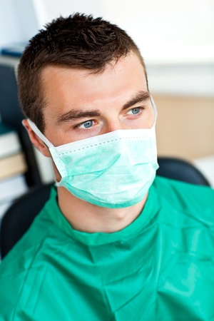 Serious male surgeon with mask and scrubs  photo