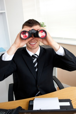 Smiling businesswoman with binoculars  photo