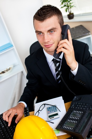 Caucasian young businessman talking on phone sitting at his desk  photo