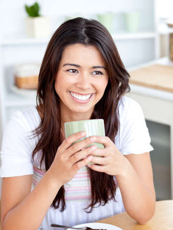 Beautiful asian woman holding a cup sitting in the kitchen  photo