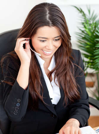 Self-assured asian businesswoman wearing headphones photo