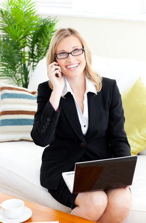 businessowman: Ambitious businessowman talking on phone using her laptop