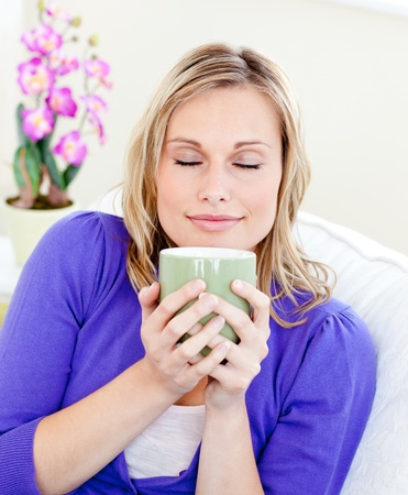 Caucasian blond woman enjoy her coffee sitting on the sofa photo