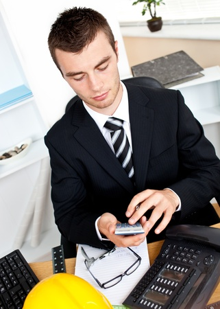 Confident businessman using his calculator sitting in his office photo