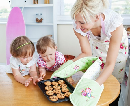 Pretty woman baking cookies with her daughter photo