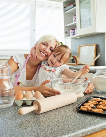 baking cookies: Laughing woman baking cookies with her daughter Stock Photo