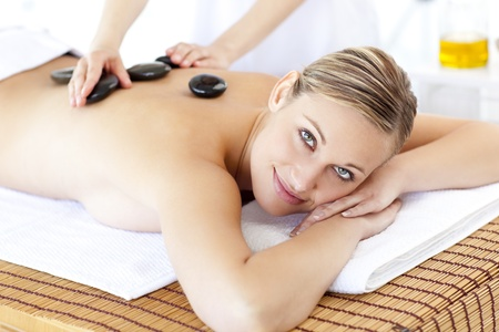 Smiling caucasian woman receiving a massage with hot stone Stock Photo - 10133304