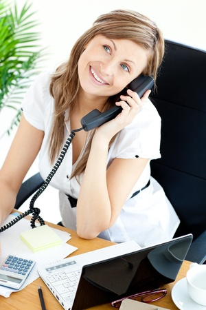 Self-assured businesswoman talking on phone sitting at her desk Stock Photo - 10133366