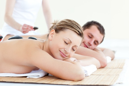 alternative wellness: Caucasian young couple having a massage with hot stone Stock Photo