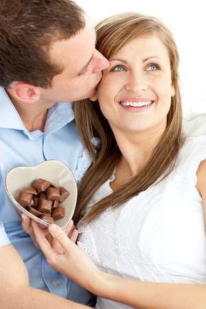 captivating: Handsome man kissing his girlfriend holding chocolote sitting Stock Photo