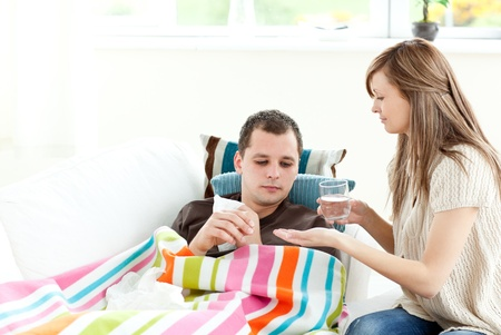 Caring girlfriend giving his sick boyfriend pill photo