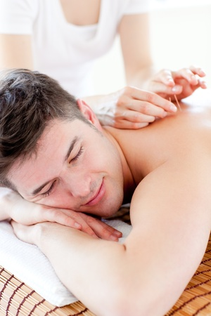 Charming young man in an acupuncture therapy in a Spa center  photo