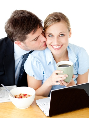 Attractive  businessman kissing his girlfriend while having breakfast photo