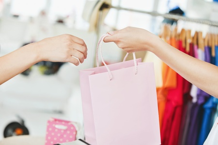 saleswomen: A saleswoman giving a shopping bag to a customer