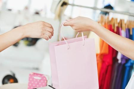 maquina registradora: Una vendedora dando una bolsa de la compra a un cliente