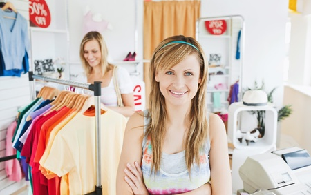 Delighted young woman smiling at the camera doing shopping with her friend photo