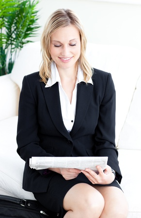 assertive: Assertive blond businesswoman reading the newspaper on a sofa Stock Photo