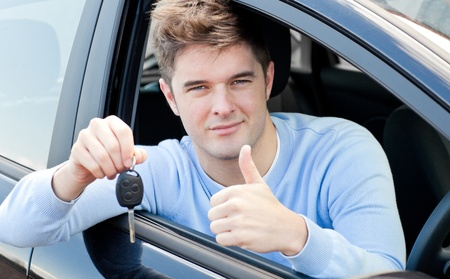 Positive young man holding a key sitting in a car  photo