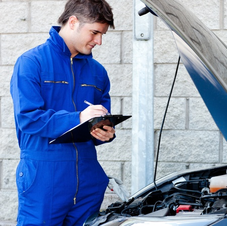 clipboard: Handsome mechanic writing on a clipboard