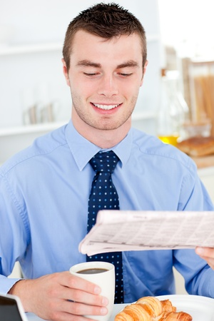 Happy businessman reading the newspaper drinking coffee photo