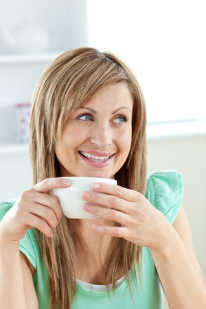 Charming caucasian woman holding a cup of coffee sitting in the ktichen Stock Photo - 10134160