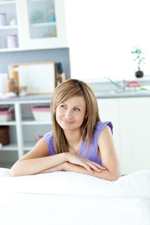 captivating: Captivating caucasian woman sitting on a sofa looking to the side