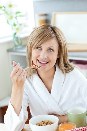 Bright woman eating cereals wearing a bath robe photo