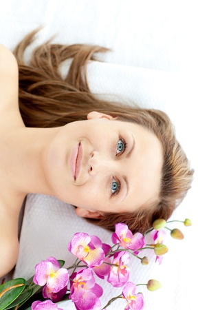 captivating: Captivating young woman lying on a massage table with flowers