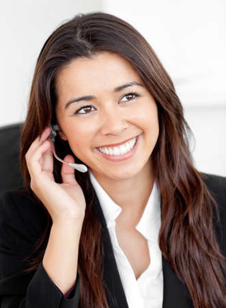 Portrait of an attractive asian businesswoman talking on phone with headphones sitting Stock Photo - 10131243