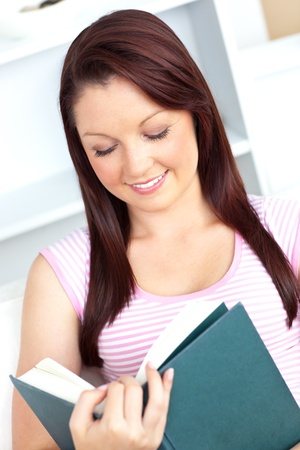 blissful: Blissful young woman reading a book sitting on the sofa  Stock Photo