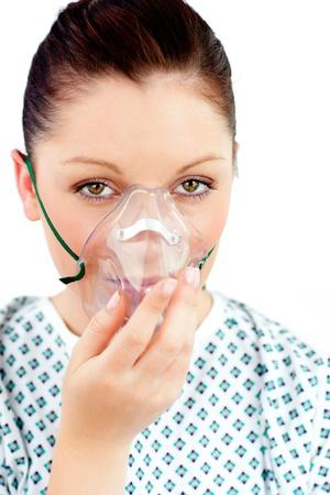 masked woman: Mujer enferma joven con una m�scara de ox�geno mirando a la c�mara Foto de archivo